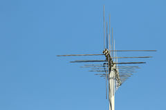 Communications antenna background. Modern crossed communications antenna stack on metal pole against blue skies with space for copy Stock Photo