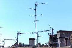 Communications antennae on a rooftop. Communications antennae for receiving television and radio transmissions on a rooftop against a clear blue sky royalty free stock images