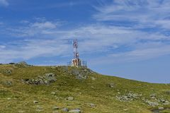 Communications cellular telecoms communications antenna in the top of the mountains with rusty communication shelter . Telecommunications Antenna against a Stock Photography