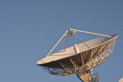 Communications dish. Large white satellite communications dish pointing upwards towards a clear blue sky Stock Photos