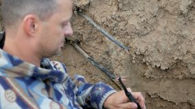 The communications engineer works with an optical cable. Lying in the ground stock video