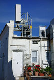 Communications Equipment on Residential Building. Communications equipment on top of older style residential building with colourful flowers in pots on rear Stock Photo