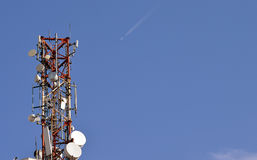 Communications: mobile telephony equipment and plane. Communications: a tower with microwave and mobile telephony transmitters and repeaters on a tall building Royalty Free Stock Photography