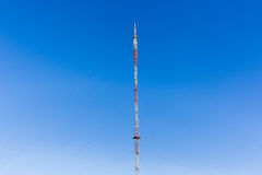 Communications Signal Tower Hilltop. Communications signal tower tall high structure,on highground hilltop for radio tv mobile phones against blue sky Royalty Free Stock Photography