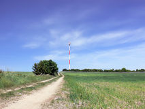 Communications tower. Landscape with a communications tower standing in the background. Field - road to the communication tower Stock Photos