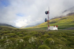 Communications tower. A communications tower in the Tundra of Iceland with a rainbow in the background Stock Photo