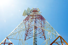 Communications tower with antennas against blue sky Stock Photo