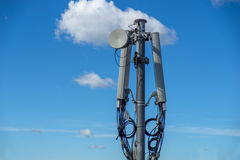 Communications tower with antennas against blue sky stock image