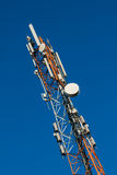Communications tower with antennas on blue sky Royalty Free Stock Photo