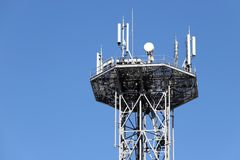 Communications tower with antennas. View of communications tower with antennas against blue sky Royalty Free Stock Photos