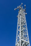 Communications tower. Bottom view of a communications tower with blue sky in the background Stock Images