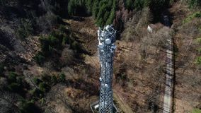 Communications tower in the forest - aerial view. Tracking shot of a communications tower in the forest - aerial view, winter time stock video footage
