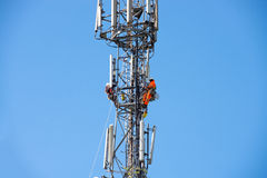 Communications Tower. WORCESTER,UK - APRIL 14 2015 : Maintenance workers carry out repairs high up on a communications tower using saftey equipment Royalty Free Stock Photo