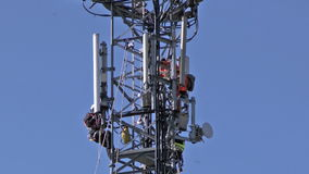 Communications Tower. WORCESTER,UK - APRIL 14 2015 : Maintenance workers carry out repairs high up on a communications tower using saftey equipment stock video