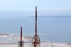 Communications towers, against the sea. A detailed view of the top part of some communications towers, landscape cut stock photography