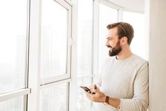 Communicative guy with beard and mustache, looking through big w. Indow while chatting or browsing internet on mobile phone Stock Photography