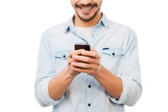Communicative person. Cropped picture of handsome young man holding mobile phone and smiling while standing against white background Royalty Free Stock Images