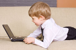 Communicative youngster. Picture of happy boy with black laptop computer Stock Photo