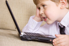 Communicative youngster. Picture of happy boy with black laptop computer Royalty Free Stock Photography