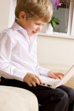 Communicative youngster. Picture of happy boy with white laptop computer Royalty Free Stock Photos