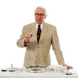 Communion. Senior pastor officiating communion with the elements before him and a wine cup in his hand Stock Photography