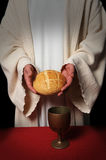 Communion. Jesus hands holding the bread at the Communion table Royalty Free Stock Image