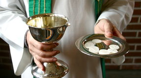 Communion. Wine and bread in the hands of a pastor or priest Stock Photo