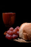 Communion. Elements of grapes, cup, bread, and wheat on a black background Royalty Free Stock Photo