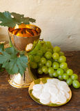 Communion bread and wine. Holy communion image showing a golden chalice with grapes and bread wafers Stock Photography
