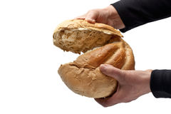 Communion - Breaking Bread. An elderly woman breaking a loaf of bread. Could be used either for Lord's Supper or feeding the needy. Over white with copy space Stock Photo
