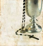 Communion Chalice and Rosary. Chalice for communion and a rosary on a grunge background royalty free stock photo