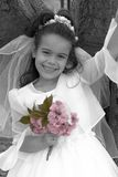 Communion Girl. Black and white portrait of little girl in communion dress and veil with pink flowers Stock Photography