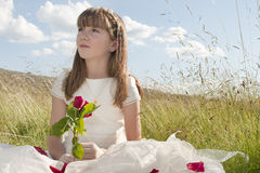 Communion girl with a rose. Girl wearing first communion dress in the meadow Royalty Free Stock Photography