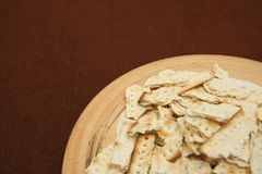 Communion Plate. A handmade ceramic communion plate with broken pieces of matzoh-type unleavened bread sits on a brown felt table cloth. plenty of copy space royalty free stock image