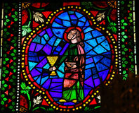 Communion. Stained glass window depicting a saint holding the Eucharist and a cup of wine in the cathedral of Leon, Castille and Leon, Spain royalty free stock images