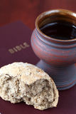 Communion still life. Chalice with red wine and bread on a Bible. Shallow dof, copy space Stock Images