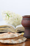 Communion still life. Chalice with red wine, pita bread, Holy Bible and white hyacinth Stock Photos
