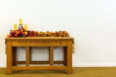 Communion table decorated with candles and colored leaves on a isolated background. Communion table at a church decorated for the fall with candles and colored royalty free stock photography