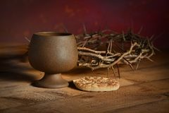 Communion Table with Wine and BRead. Communion table with bread and cup of wine and crown of thorns in background royalty free stock photography