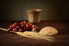 Communion Table With Wine Bread Grapes and Wheat. Cup of wine, red grapes, bread and wheat as symbols of Communion Royalty Free Stock Photo