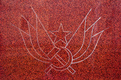 Communism and socialism. Commemorative plaque with star, wings, hammer and sickle on dark red background. Symbol of communism, socialism and its emancipatory royalty free stock images