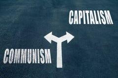 Communism vs capitalism choice concept. Two direction arrows on asphalt royalty free stock photos