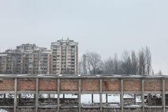 Communist housing buildings in front of an abandoned warehouse in Pancevo, Serbia, during a cold afternoon under the snow. This kind of towers are a symbol of Royalty Free Stock Image