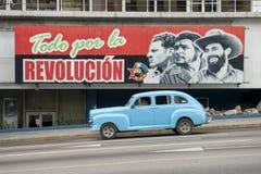 Communist Propaganda Billboard and Car in Havana Cuba. HAVANA, CUBA - CIRCA JUNE, 2011: Vintage American taxi car passes below billboard promoting Communist royalty free stock photos