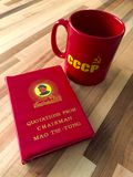 Communist red book and mug. Little red book of quotations by Chairman Mao Tse-Tung and red mug of Soviet era with hammer and sickle symbol, wooden background Royalty Free Stock Photo