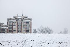 Communistische huisvestingsgebouwen voor een bevroren heuvel in Pancevo, Servië, tijdens een middag met sneeuw Stock Foto's