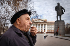 Communists party in a May Day. Old man smokes a cigarette near the monument to Lenin Stock Image