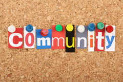 Community. The word Community in cut out magazine letters pinned to a cork notice board with push pins Stock Photography