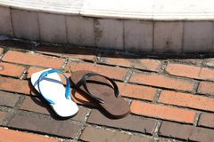 Community. Two different flip-flops used as a pair Stock Photo