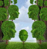 Community Assistance. And public support concept as a group of adult human head shaped trees giving help to a young child plant as a nurturing metaphor for Stock Image